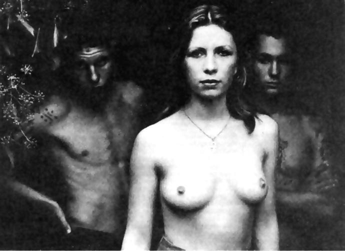 Femme seins nus entre 2 hommes torse nu