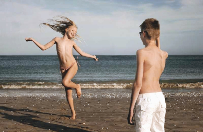 fille-danse-devant-un-garcon-a-la-plage